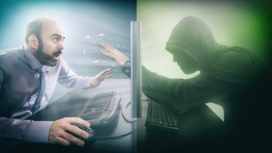 Hacker reaches hand through computer to simulate a phishing attack.