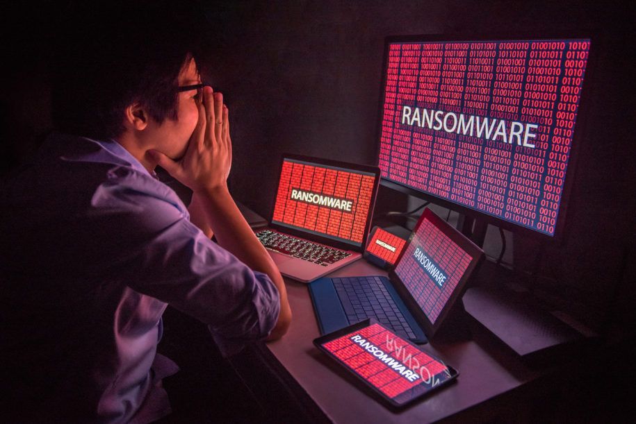 Man surrounded by computers with screens showing the impacts of ransomware.